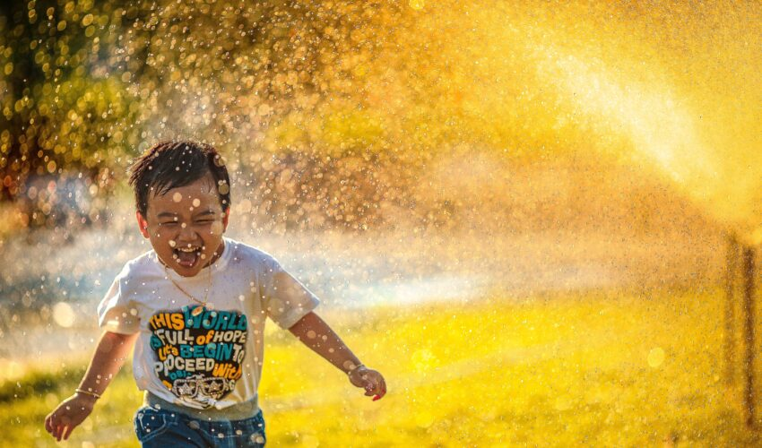 young boy running through sprinkler